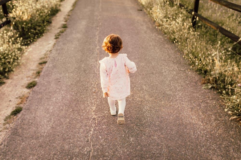 道を一人で子どもが歩いている