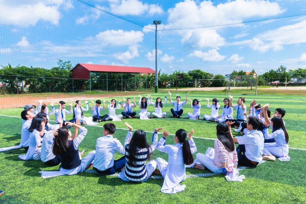 芝生の上で円になって集まる学生