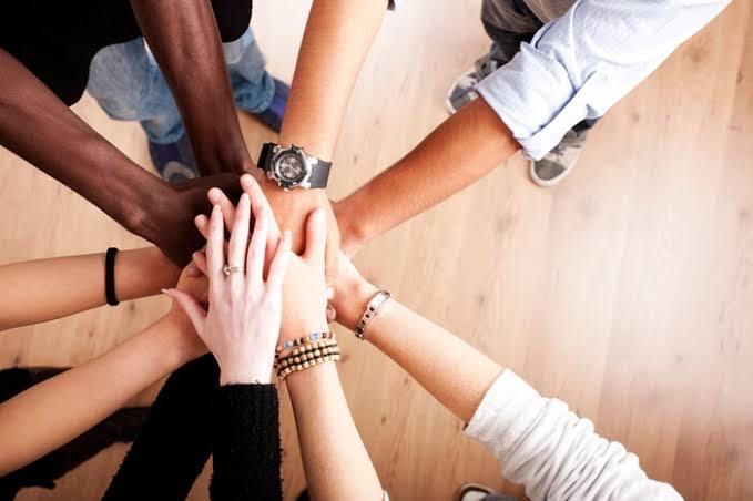 手を合わせて集合している人達