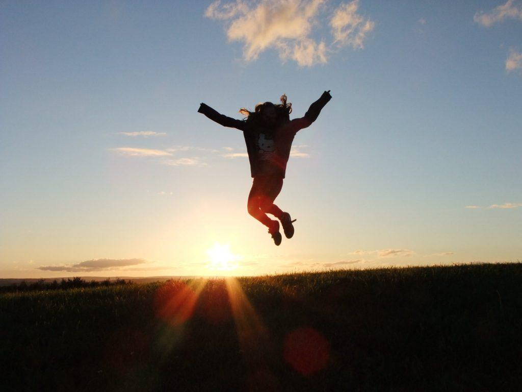 夕焼けをバックに飛び跳ねる女性